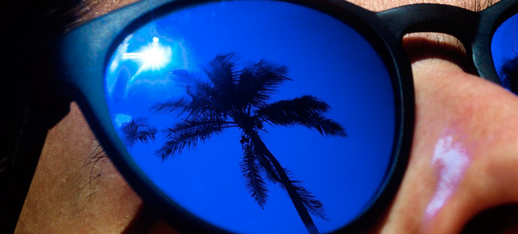 Face of a man wearing blue mirror sunglasses, reflecting a sun.
